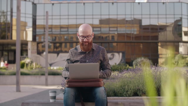 hipster businessman with a laptop working outdoors - bench stock videos & royalty-free footage