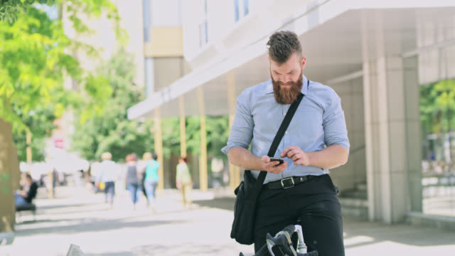 DS Hipster checking his smart phone while riding his bicycle in the city video