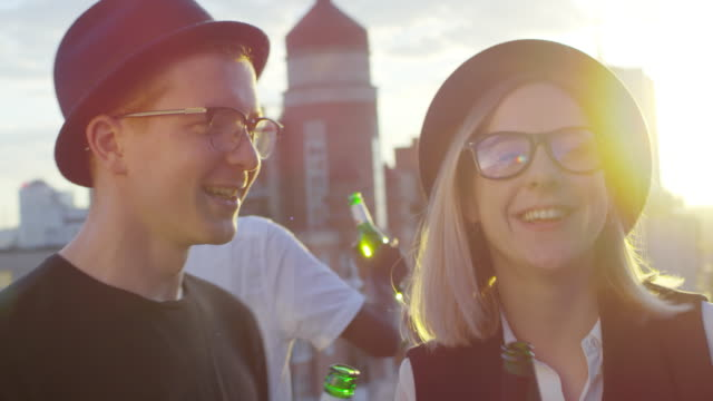Hipster Couple Drinking and Dancing at Party on Rooftop