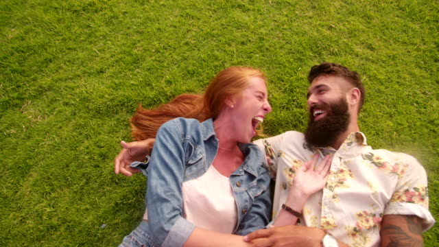 Hipster couple lying on grass affectionately laughing video