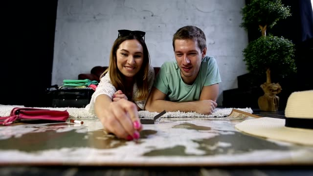 Hipster couple placing pins on scratch travel map video