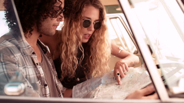 Hipster Couple Sitting in Van Looking at Road Trip Map Window perspective of Hipster mixed race man and hipster caucasian woman holding open a map and looking at it in the front seat of a retro van california map stock videos & royalty-free footage