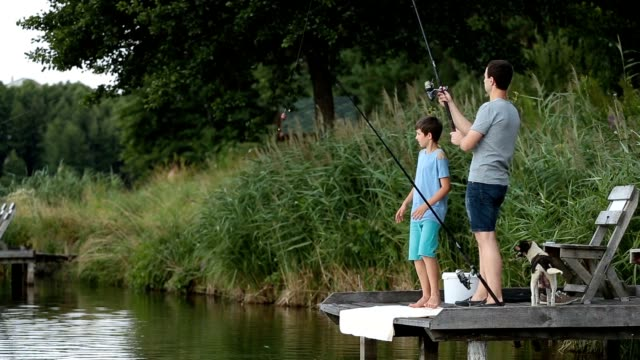 hipster dad and boy enjoying fishing at the pond - пруд стоковые видео и кадры b-roll