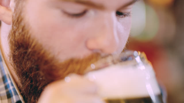 ecu hipster drinking a beer in the pub - baffo peluria del viso video stock e b–roll