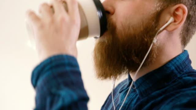 Hipster tomando café en el escritorio en la oficina creativa - vídeo