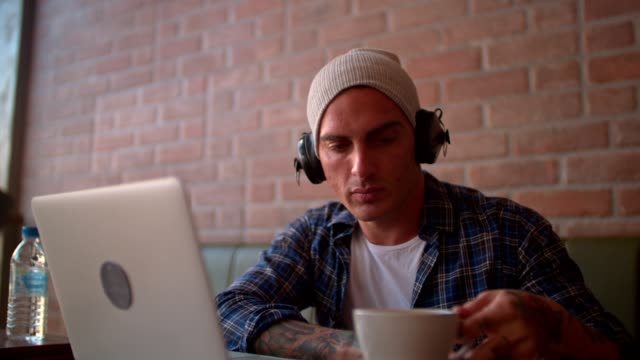 Hipster drinking coffee, listening to music and looking at laptop video