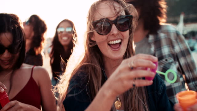 Hipster friend partying with bubbles at the harbor on sunset video