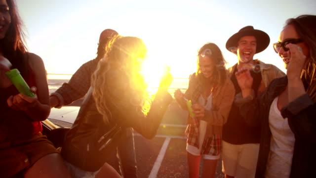 Hipster amico feste con le bollicine sul lungomare al tramonto - video