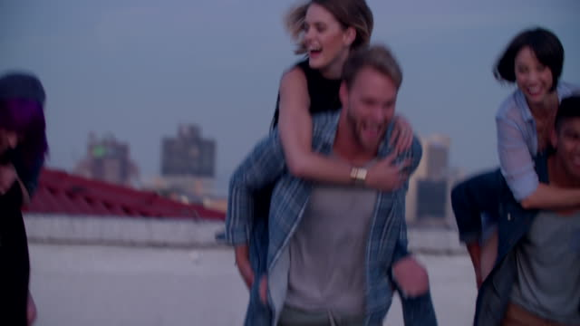 Hipster friends doing funny piggyback rides on rooftop video