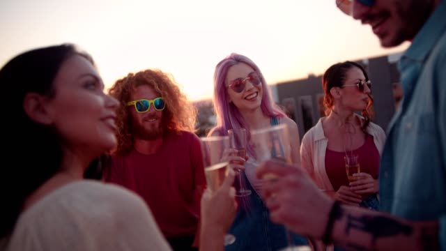 Hipster friends drinking champagne and flirting at rooftop summer party video