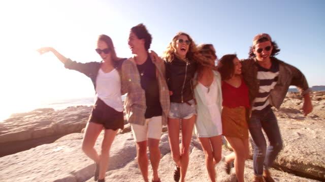 Hipster friends embracing joyfully on seaside video