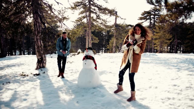 Hipster friends having fun with snowball fight in the snow Young couple having fun playing snowball fight in snow covered mountain forest with snowman snowman stock videos & royalty-free footage