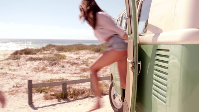 hipster gli amici di saltare di viaggio van in spiaggia - furgone video stock e b–roll
