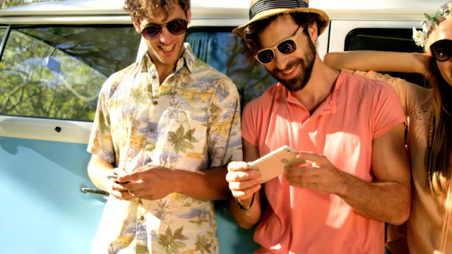 Hipster friends looking at smartphone and laughing video