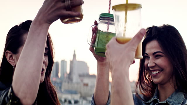 vidéos et rushes de réunion d'amis de hipster sur un toit. boire des boissons d'été - man drinking terrace