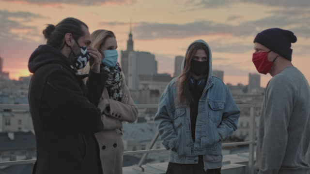 Hipster friends meeting on a rooftop. Social life during pandemic Young people meeting on a rooftop. Wearing masks and keeping distance covid mask stock videos & royalty-free footage