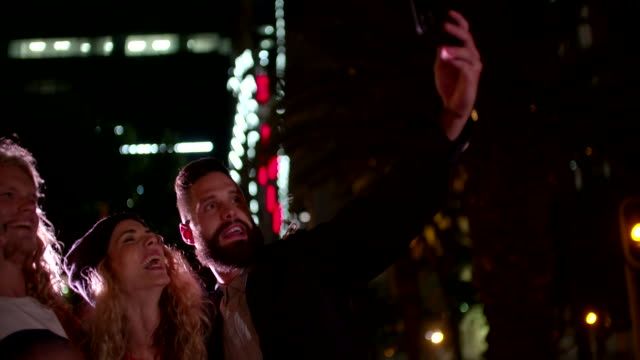 Hipster friends taking a night selfie in town video