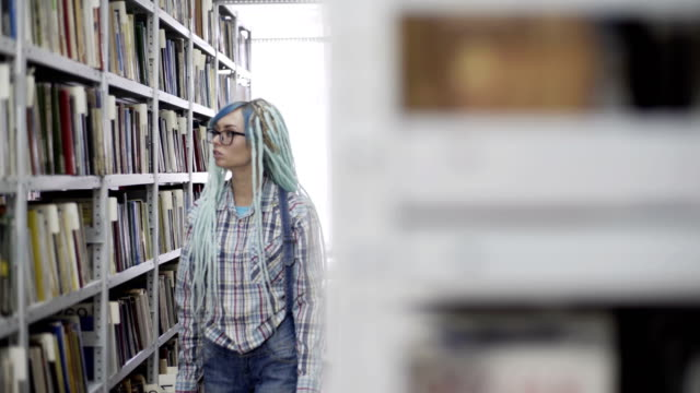 Hipster girl absorbed in reading book in library Portrait of a hipster woman reading book in library blue hair stock videos & royalty-free footage