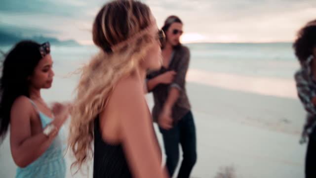 Fricchettone ragazza ballando sulla spiaggia con gli amici in riva al mare - video