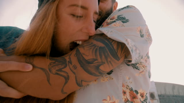 Hipster girl playfully pretending to bite her boyfriend's tattooed arm Playful hipster girl pretending to take big bite out of her boyfriend's tattooed arm while hanging out at the beach tattoo stock videos & royalty-free footage