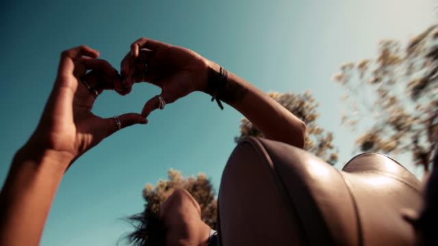 vídeos de stock, filmes e b-roll de garota hipster posando para foto a mão no coração - boho