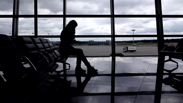 hipster girl sit on chair at airport lounge and texting on smartphone - аэровокзал стоковые видео и кадры b-roll