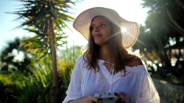 ヤシの木の下で写真を撮って内気な少女 - ビジネスマン点の映像素材/bロール
