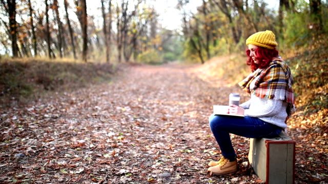 hipster girl with coffee cup and book, sitting on suitcase video