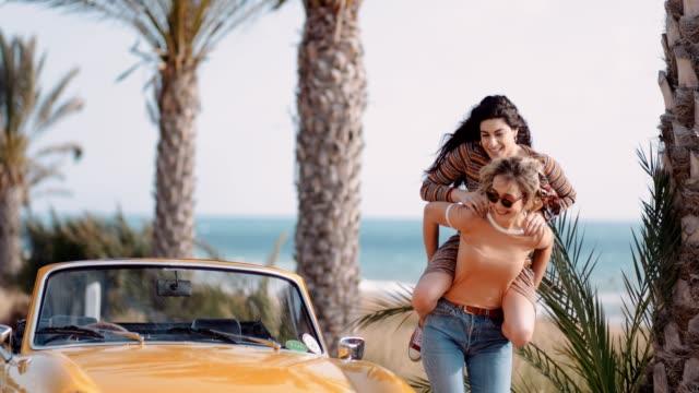 Hipster girls having fun with piggyback ride on road trip
