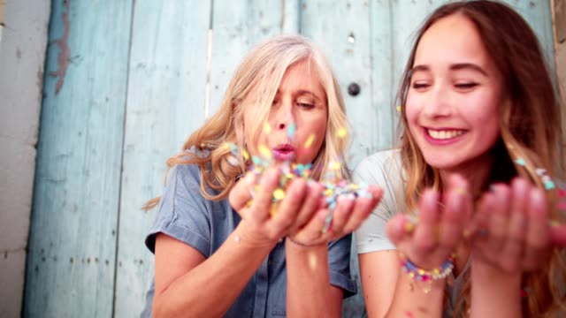 hipster granddaughter and grandmother celebrating blowing confetti in old town - mothers day stock videos & royalty-free footage