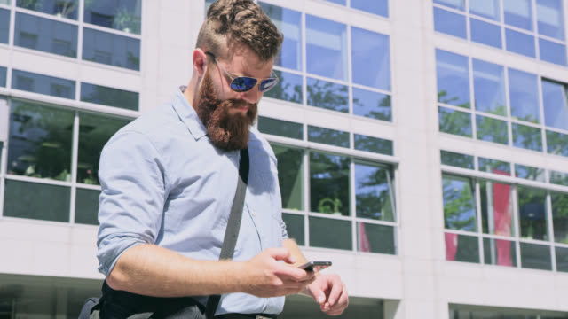 DS Hipster in shirt using a smart phone in front of the office building video