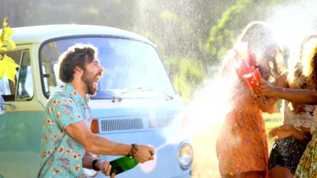 割れヒップスター男彼は友人にシャンパンのボトルを開ける ビデオ