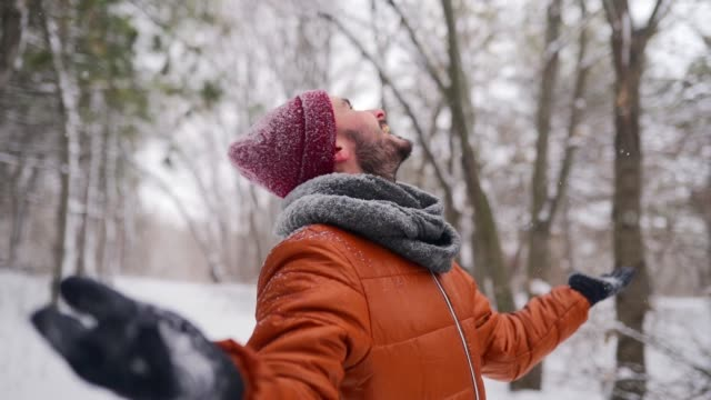 Hipster man enjoying falling snow outdoors on winter day on Christmas vacation. Happy guy open arms under snowfall in park and catch the snowflakes with hands and tongue. Male stretch out arms to sky