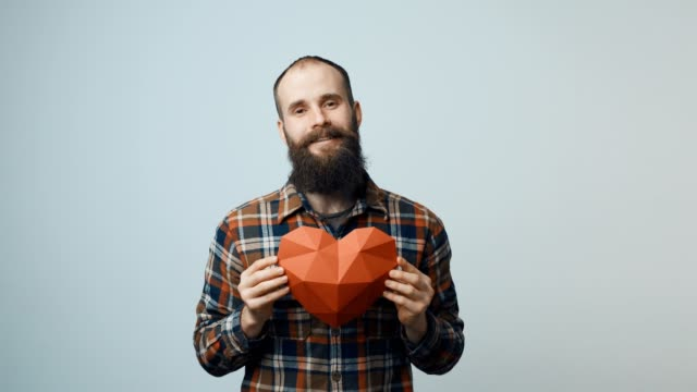 Hipster man holding heart shape in hands