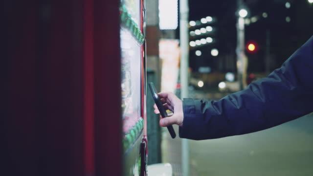 ็Hipster man paying with smartphone to vending machine. Asian man selecting some drink at vending machine contactless payment stock videos & royalty-free footage