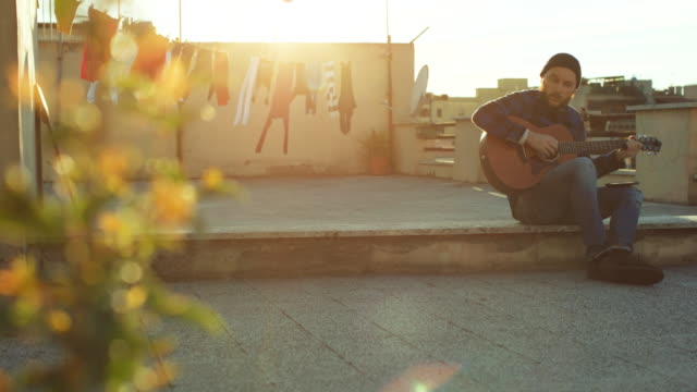 hipster man playing acoustic guitar on the terrace - balcone video stock e b–roll