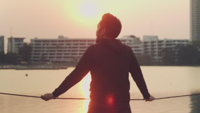 vídeos de stock e filmes b-roll de hipster man standing at river and enjoying breathtaking view at sunset - capuz