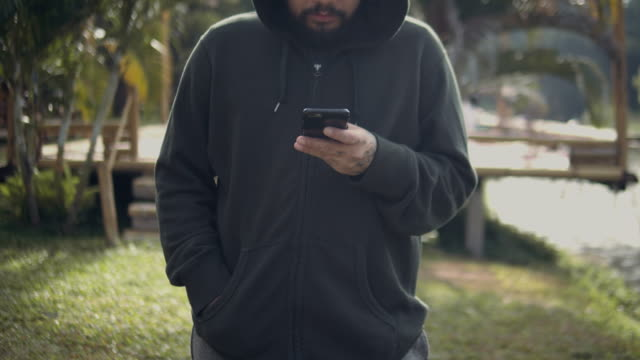 hipster adam manifatura yaptığı telefon sabah park'ta. - kapüşon stok videoları ve detay görüntü çekimi