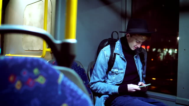 Hipster man texts messages in bus Young man using smart phone during bus ride at night. bus stock videos & royalty-free footage