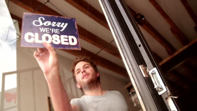 hipster man turning opening sign on door coffee shop - open sign stock videos & royalty-free footage