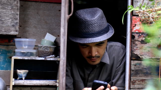 hipster man use smartphone on the window architrave video