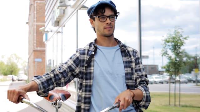 hipster uomo che cammina con bici a ingranaggi fissi su strada - berretto video stock e b–roll