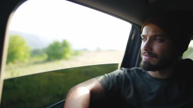 vídeos y material grabado en eventos de stock de hombre hipster con tapa de punto que conduce en el asiento trasero en el coche - uso compartido del coche