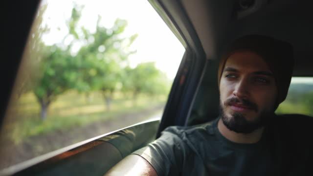 uomo hipster con berretto a maglia che guida sul sedile posteriore in auto - barba peluria del viso video stock e b–roll