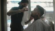 istock Hipster men cutting hair to customer. 1270830574