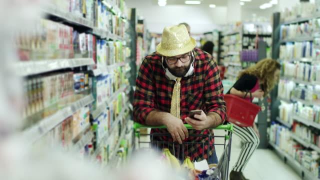 Hipster men using smartphone in supermarket video