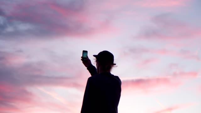 옥상에서 힙스터 또는 밀레니얼 영화 일몰 - influencer 스톡 비디오 및 b-롤 화면