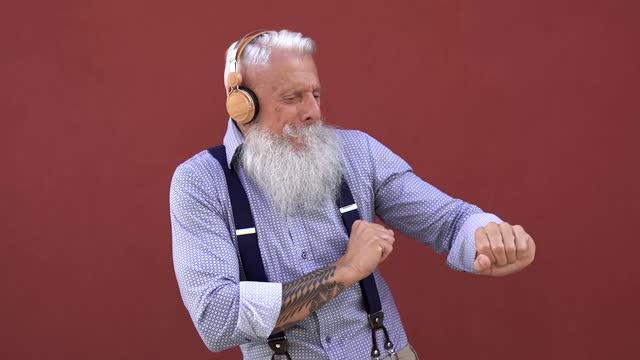 ワイヤレスヘッドフォンを身に着けている音楽プレイリストに踊るヒップスターシニアマン - 高齢者は技術を楽しむ - あごヒゲ点の映像素材/bロール