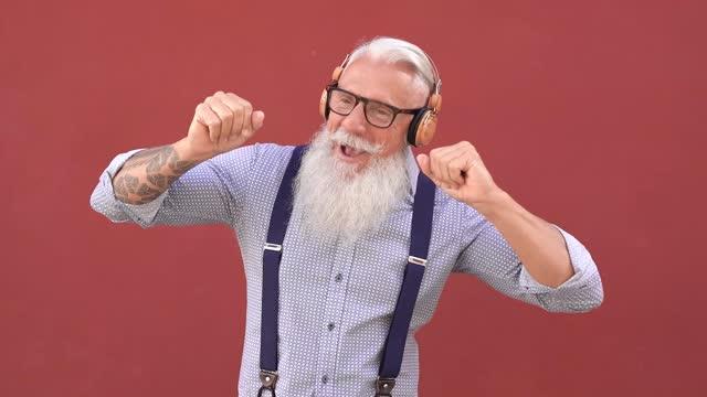 屋外でプレイリスト音楽に踊るヒップスターシニアマン - 高齢者は技術を楽しむ - あごヒゲ点の映像素材/bロール