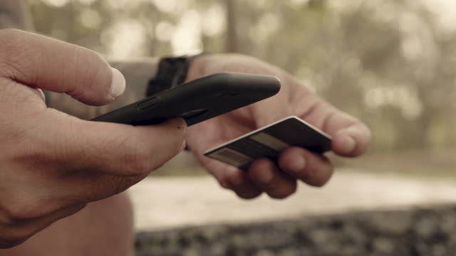 vídeos de stock e filmes b-roll de hipster sitting on bench and using phone with credit card. - atividade comercial